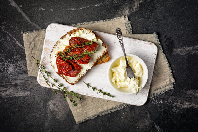 Top view of tasty sandwiche with healthy bread, soft cheese and sun-dried tomatoes on black marble background